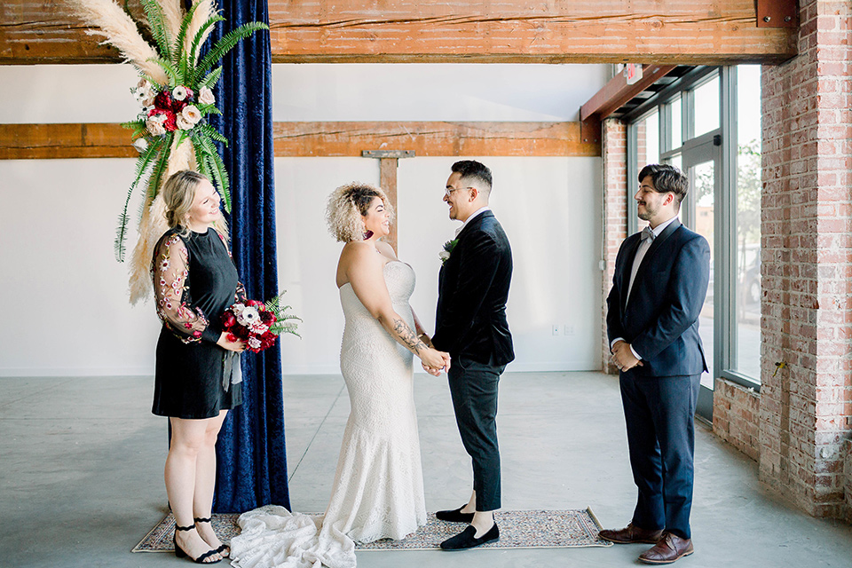 the bride is in a white formfitting lace gown with a sweetheart neckline and fun velvet shoes and the groom in a black velvet tuxedo with a cropped pant and bow tie at ceremony