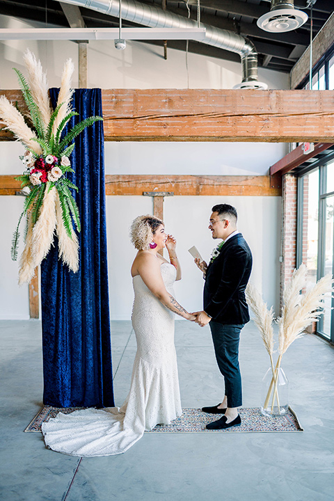 the bride is in a white formfitting lace gown with a sweetheart neckline and fun velvet shoes and the groom in a black velvet tuxedo with a cropped pant and bow tie together at the ceremony