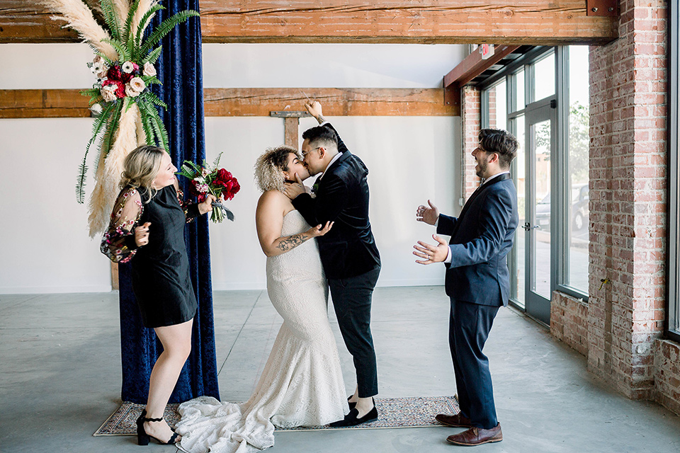 the bride is in a white formfitting lace gown with a sweetheart neckline and fun velvet shoes and the groom in a black velvet tuxedo with a cropped pant and bow tie exchanging rings