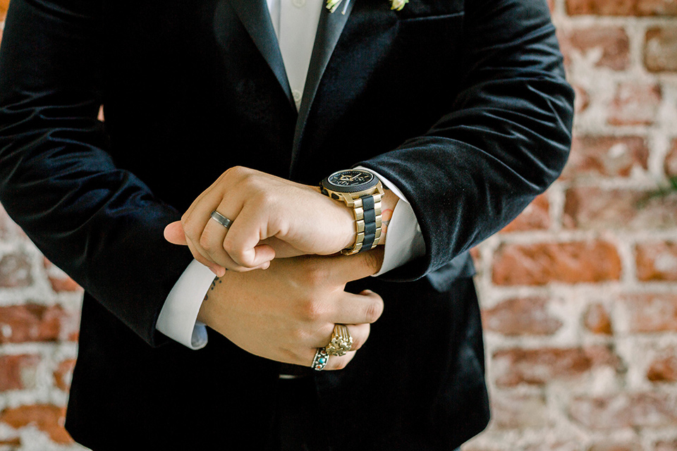 the groom in a black velvet tuxedo with a cropped pant and bow tie exchanging rings