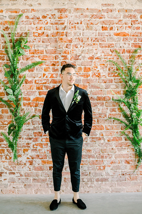 groom in a black velvet tuxedo with a cropped pant and bow tie