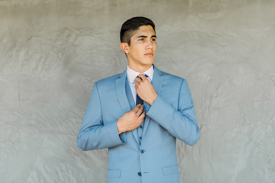 chambelan in a light blue suit and navy long tie and blue pocket square