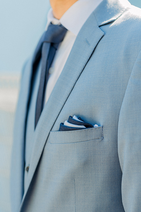 light blue suit with a navy long tie and pocket square