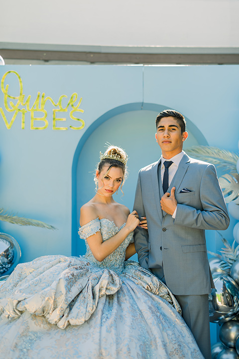 birthday girl in a light blue gown and a strapless neckline and the chambelanes in a light blue suit with a navy long tie