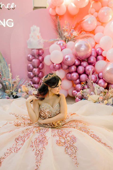 birthday girl at her quince party with her gold and pink gown