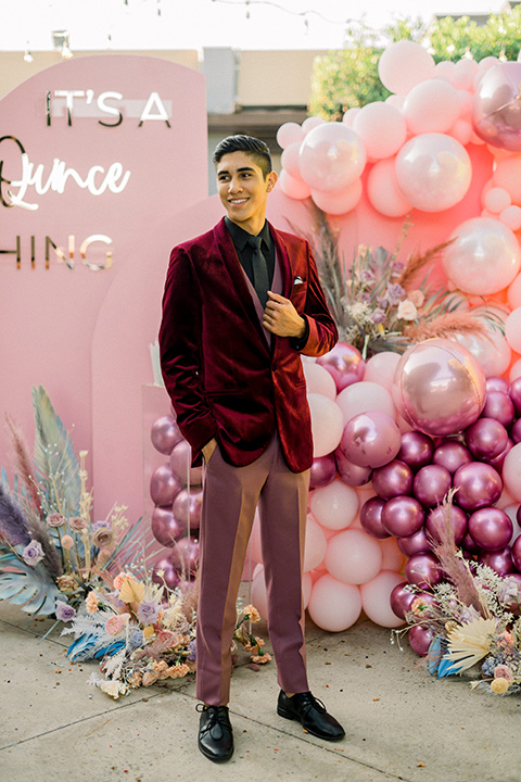 chambelanes style with a burgundy velvet tuxedo, rose pink pants and vest, and a black shirt