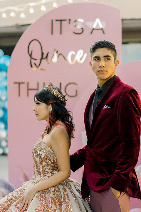 chambelanes style with a burgundy velvet tuxedo, rose pink pants and vest, and a black shirt and the birthday girl in a gold and pink gown with a strapless neckline and lace detailing