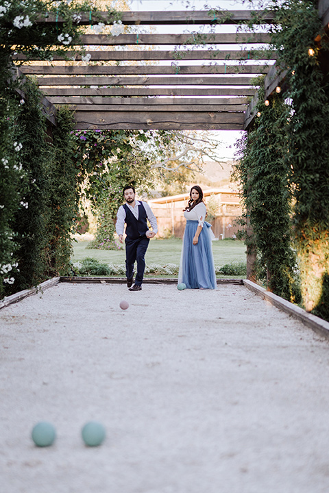 bride in a two-piece gown with a cream top and blue tulle skirt, and the groom in a navy notch lapel suit with a navy tie – playing outdoor games together