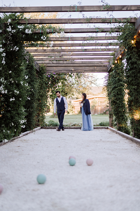 bride in a two-piece gown with a cream top and blue tulle skirt, and the groom in a navy notch lapel suit with a navy tie – playing outdoor games