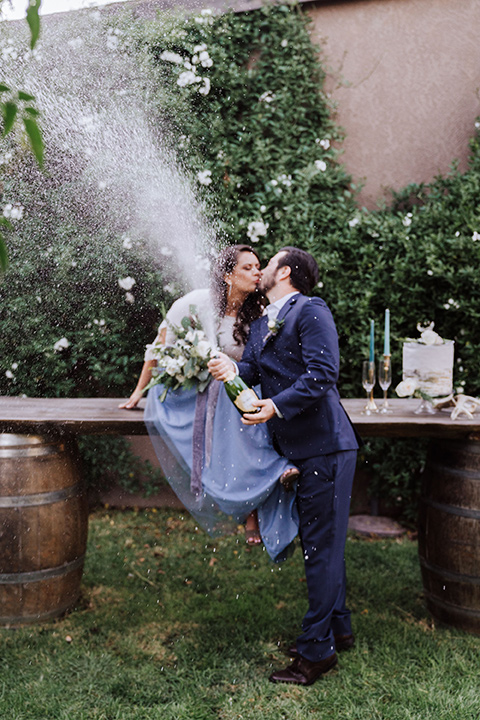 bride in a two-piece gown with a cream top and blue tulle skirt, and the groom in a navy notch lapel suit with a navy tie – spraying champagne