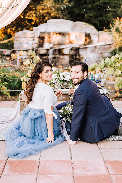bride in a two-piece gown with a cream top and blue tulle skirt, and the groom in a navy notch lapel suit with a navy tie – sitting down at table together