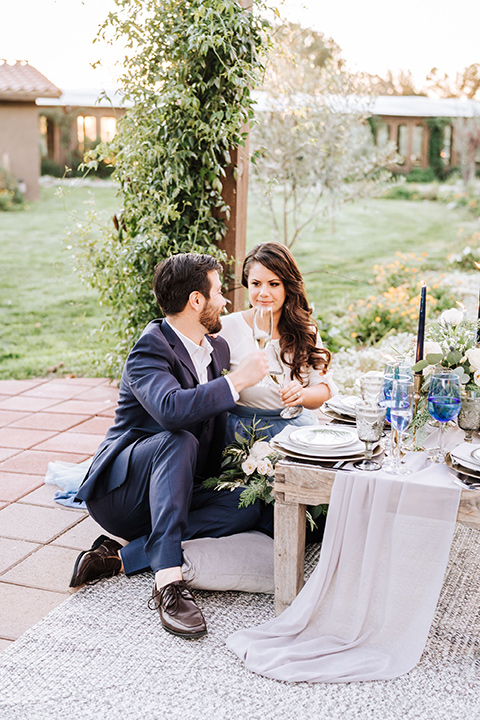bride in a two-piece gown with a cream top and blue tulle skirt, and the groom in a navy notch lapel suit with a navy tie – at sweetheart table