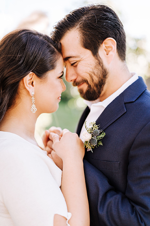 bride in a two-piece gown with a cream top and blue tulle skirt, and the groom in a navy notch lapel suit with a navy tie – touching heads