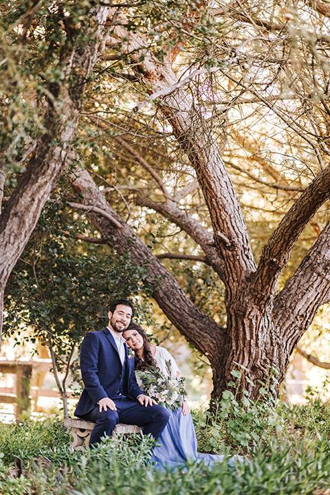 bride in a two-piece gown with a cream top and blue tulle skirt, and the groom in a navy notch lapel suit with a navy tie – under the trees