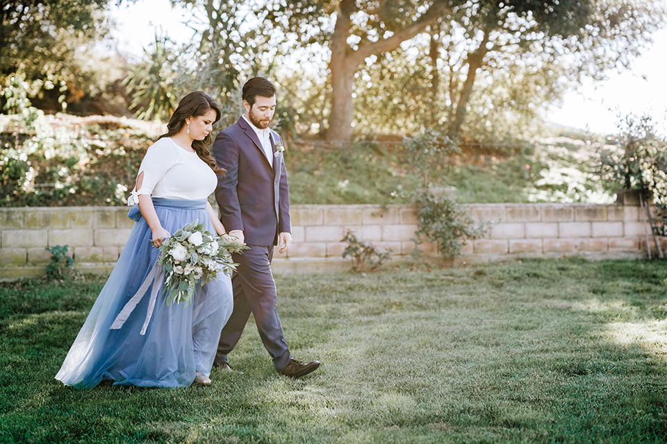 bride in a two-piece gown with a cream top and blue tulle skirt, and the groom in a navy notch lapel suit with a navy tie – walking together