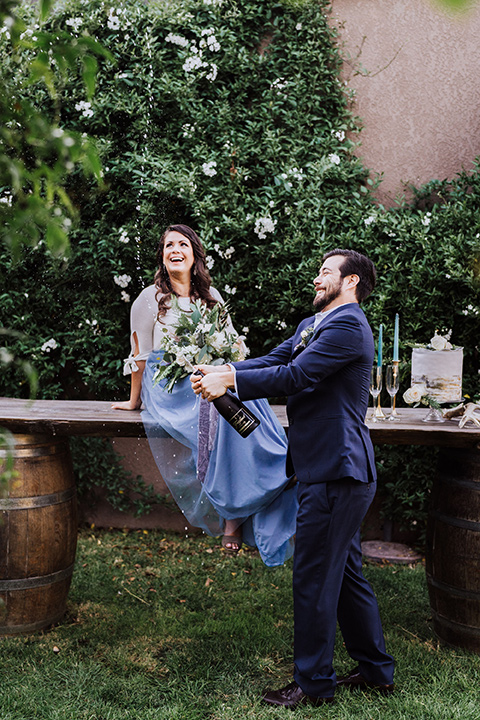 bride in a two-piece gown with a cream top and blue tulle skirt, and the groom in a navy notch lapel suit with a navy tie – pouring champagne