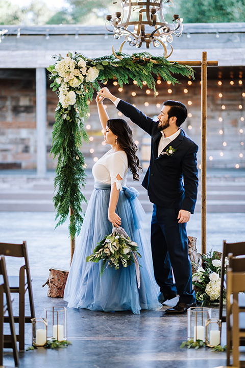 bride in a two-piece gown with a cream top and blue tulle skirt, and the groom in a navy notch lapel suit with a navy tie – twirling at the ceremony