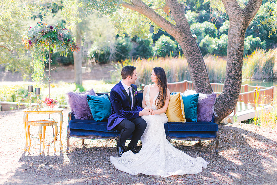 bride in a formfitting white gown with lace detailing and thin straps and the groom in a blue velvet tuxedo with a long tie sitting on the couch