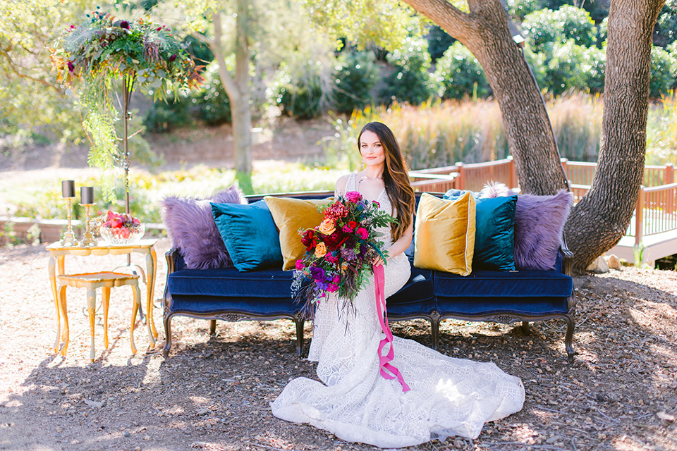 bride sitting on a velvet couch in a formfitting white gown with lace detailing and thin straps