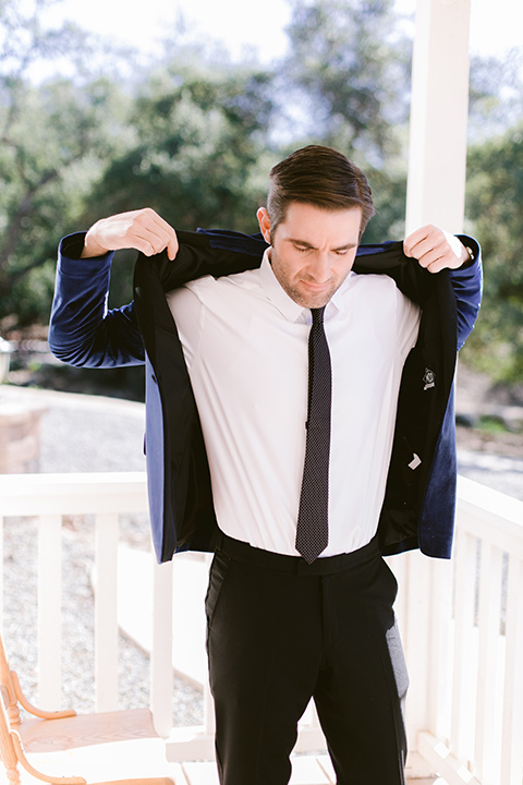 groom putting on a velvet blue jacker and black tuxedo pants