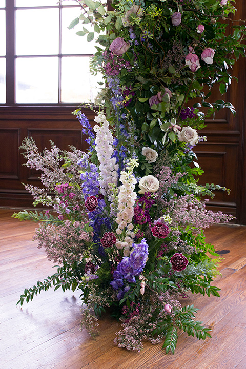 green and purple flowers on ceremony arch