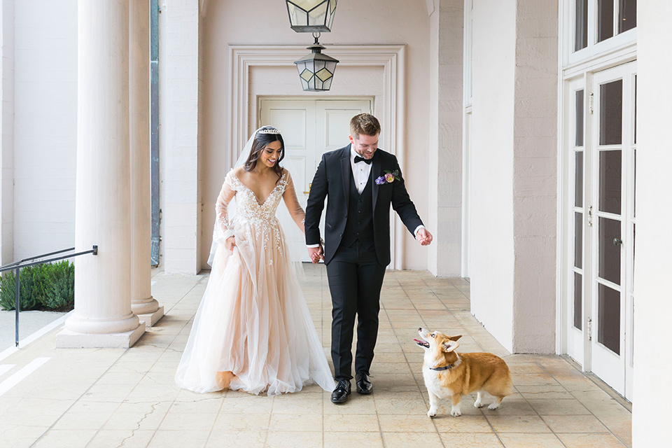 bride in a white lace ballgown with a sweetheart neckline and a regal looking crown and the groom in a black tuxedo with a black bow tie and pocket square walking their corgis