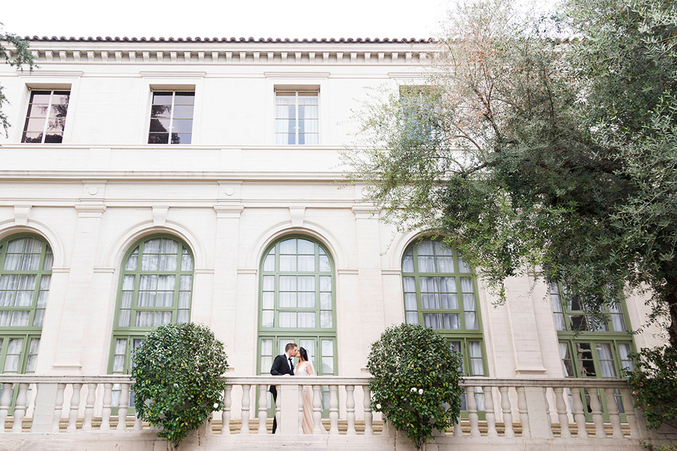 bride in a white lace ballgown with a sweetheart neckline and a regal looking crown and the groom in a black tuxedo with a black bow tie and pocket square in front of historic venue