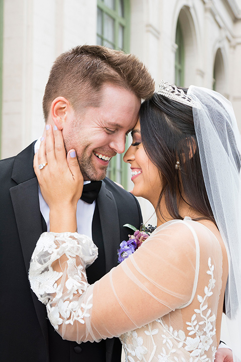 bride in a white lace ballgown with a sweetheart neckline and a regal looking crown and the groom in a black tuxedo with a black bow tie and pocket square close up