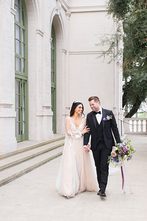 bride in a white lace ballgown with a sweetheart neckline and a regal looking crown and the groom in a black tuxedo with a black bow tie and pocket square on the steps