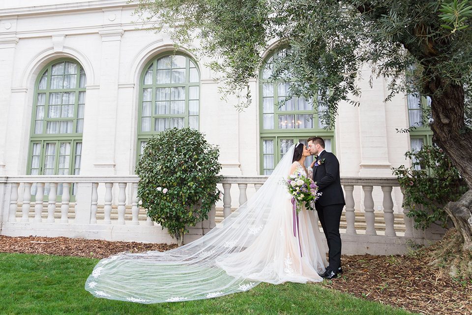 bride in a white lace ballgown with a sweetheart neckline and a regal looking crown and the groom in a black tuxedo with a black bow tie and pocket square ceremony at historic venue