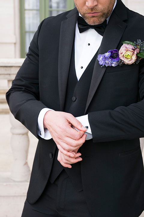 groom in a black tuxedo and a black bow tie with a purple pocket square