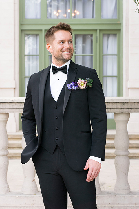 groom in a black tuxedo with a black bow tie and purple pocket square