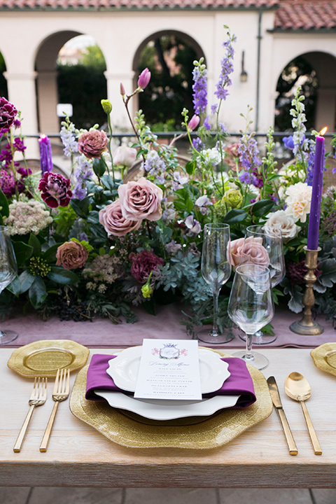white plates with royal purple linens and gold flatware