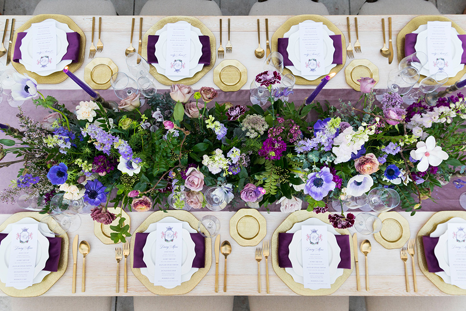 wooden table with white plates and purple linens with purple and green florals