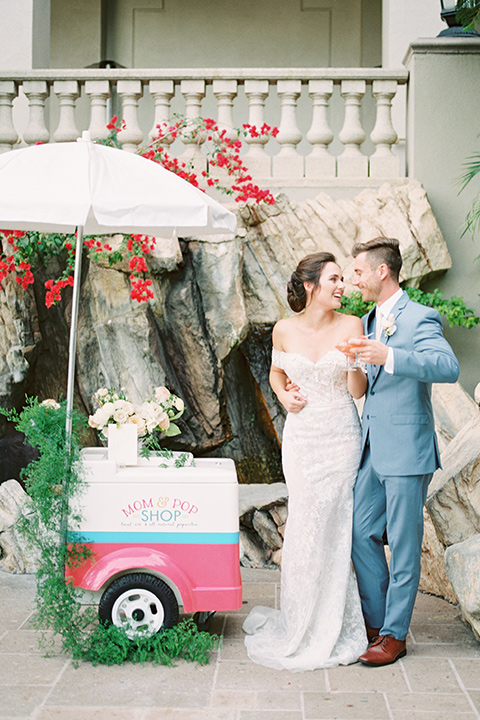 bride in a form fitting gown with an off the shoulder detail and the groom in a light blue suit next to bar cart