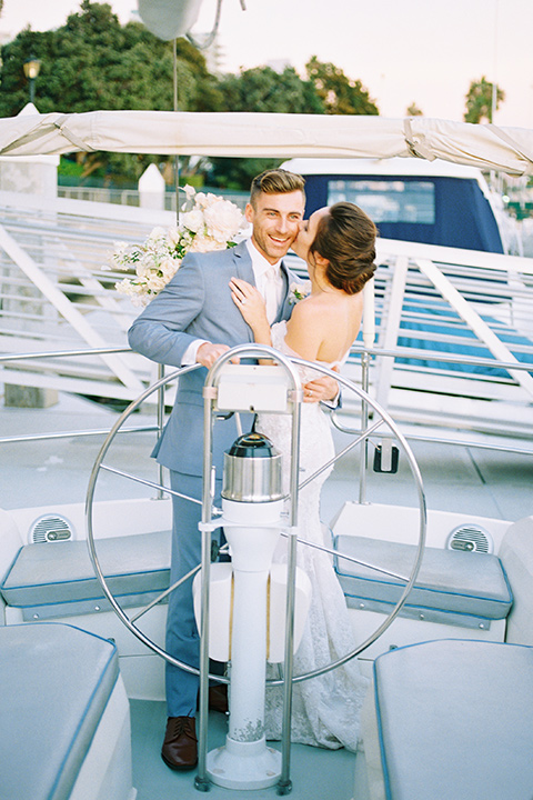 bride in a form fitting gown with an off the shoulder detail and the groom in a light blue suit on a boat