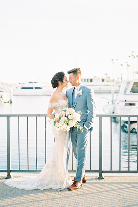 bride in a form fitting gown with an off the shoulder detail and the groom in a light blue suit by water