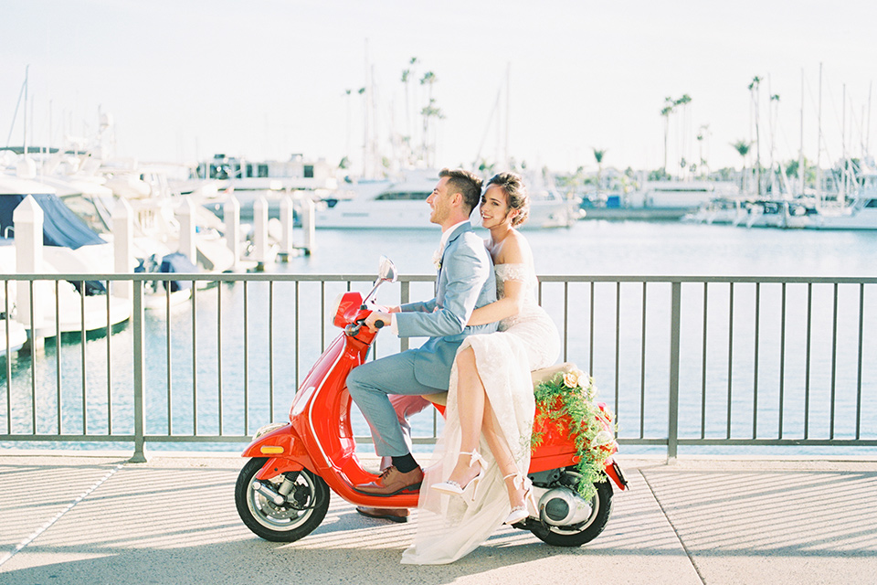 bride in a form fitting gown with an off the shoulder detail and the groom in a light blue suit on the vespa