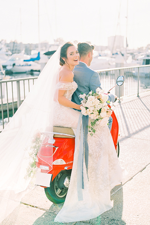 bride in a form fitting gown with an off the shoulder detail and the groom in a light blue suit with the vespa