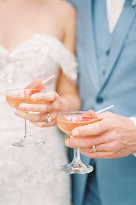 bride in a form fitting gown with an off the shoulder detail and the groom in a light blue suit next to bar cart close up on their drinks