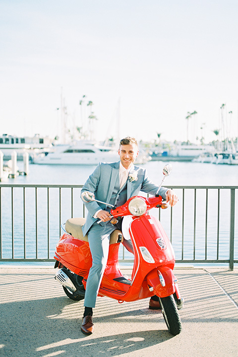 the groom in a light blue suit on a vespa