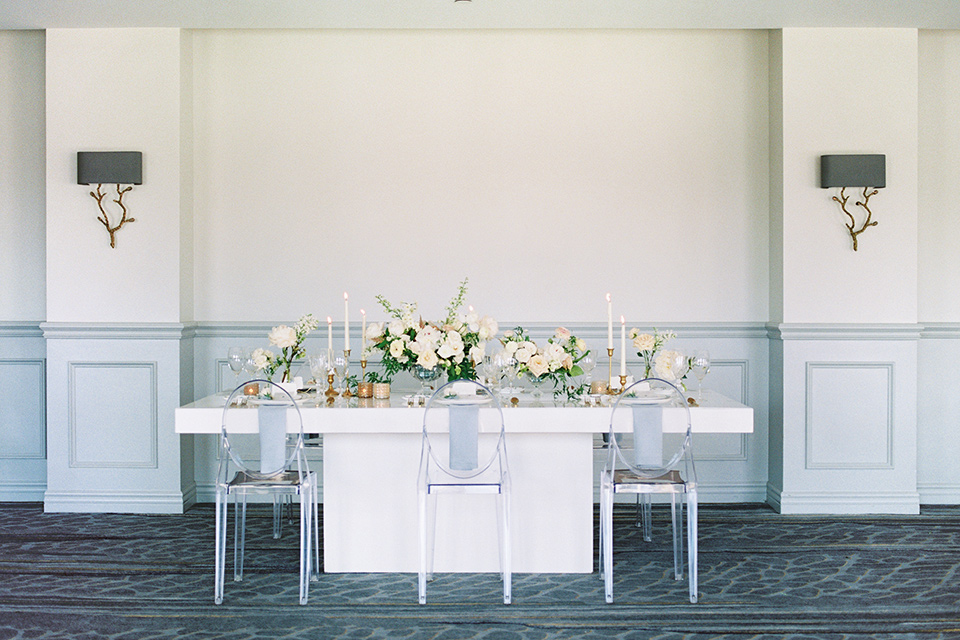 white tablescape with white chairs on it