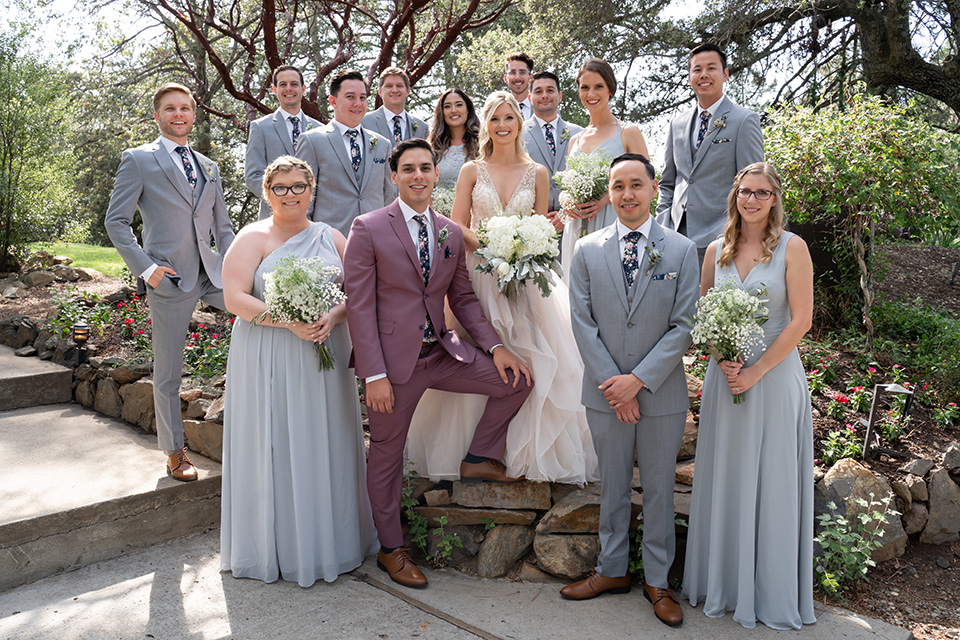 bride in a white ballgown with a deep-v neckline and crystal embellishments and the groom in a rose pink suit with a navy floral neck tie, and the bridesmaids in silver blue gowns and the groomsmen in heather grey suits with floral long ties