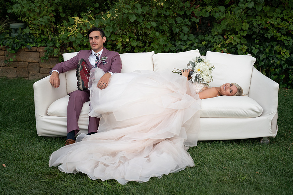 bride in a white ballgown with a deep-v neckline and crystal embellishments and the groom in a rose pink suit with a navy floral neck tie