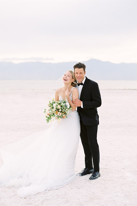 bride in a white ethereal gown with a flowing tulle train and illusion neckline and the groom in a black shawl tuxedo with a black bow tie
