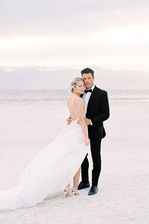 bride in a white ethereal gown with a flowing tulle train and illusion neckline and the groom in a black shawl lapel tuxedo with blacktie accessories