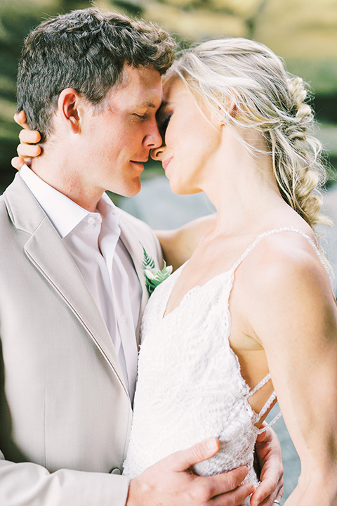 bride in a flowing blush and white gown with a silk style top and the groom in a tan suit with no tie and light brown shoes