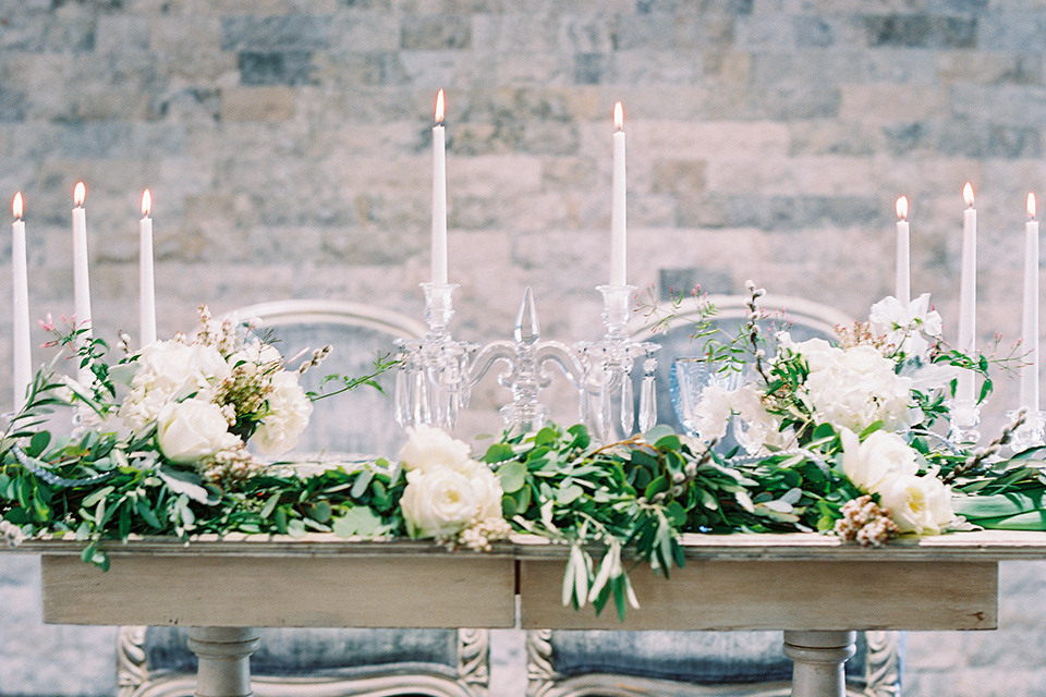 light wood table with tall white candles and greenery