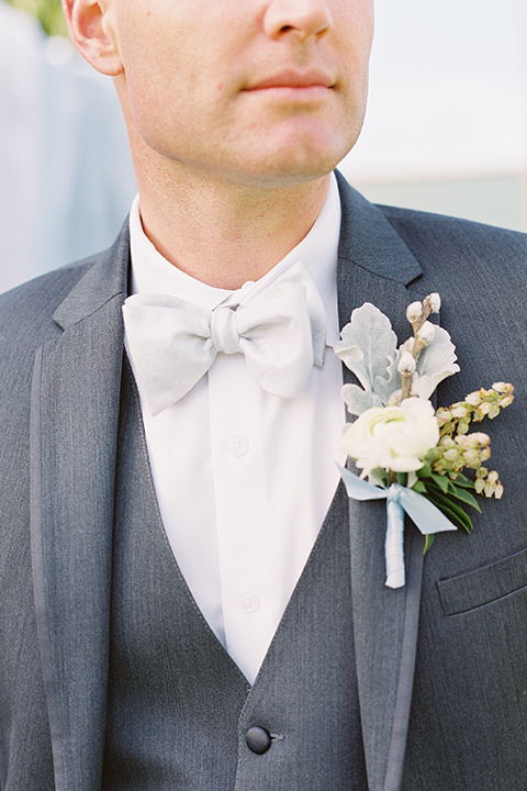 groom in a grey suit with a silver bow tie close up