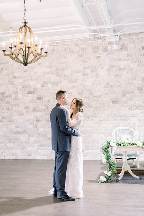 bride in a form fitting gown with an illusion back and neckline groom in a grey tuxedo with a silver bow tie first dance
